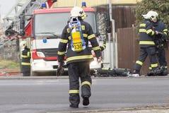 Prostejov representante 28 de enero checo - bombero que camina hacia un firetruck durante la acción de la lucha contra el fuego r Foto de archivo libre de regalías