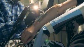 Prosthetic hand som tatueras i en salong, rörelsehindrad person lager videofilmer