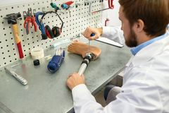 Prosthetist Making Artificial Leg. Portrait of  prosthetist at work, over the shoulder view of young man assembling artificial foot sitting at table in modern Stock Image