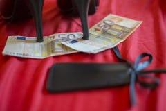 Prostituiertes oder Stripteasekonzept, Euro 50 banknot mit Sexspielzeug auf rotem Bett Stockbild