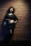 Prostitute. Portrait of girl dressed like hooker posing near brick wall Stock Images