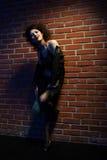 Prostitute. Portrait of girl dressed like hooker posing near brick wall Royalty Free Stock Photos