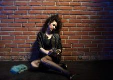 Prostitute. Portrait of girl dressed like hooker posing near brick wall Stock Photo