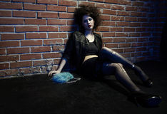 Prostitute. Portrait of girl dressed like hooker posing near brick wall Royalty Free Stock Photo