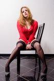 Prostitute na camisola vermelha e nas cabeçadas que sentam parcialmente despido na cadeira Foto de Stock Royalty Free