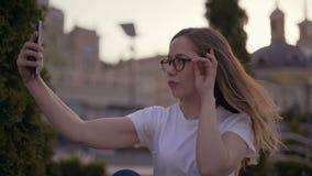Prostowłosa młoda piękna uśmiechnięta dziewczyna jest ubranym przypadkową czerwoną koszulkę outside w parku, robi selfie z smartp zdjęcie wideo
