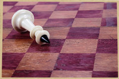Prostrate chess king. The defeat chess king against an old chessboard Royalty Free Stock Photos