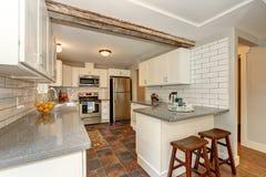Prosty mimo to praktyczny kuchenny wnętrze z białymi gabinetami obraz stock
