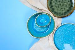 Prosty nieociosany handmade Ceramiczny tableware na błękitnym tle fotografia stock