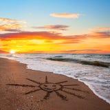 Prosty słońce rysunek w piasku na zmierzch plaży Obraz Royalty Free