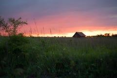 Prosty wiejski dom przy zmierzchem zdjęcie stock
