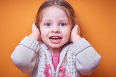 Protégez les enfants contre l'information non désirée, une petite fille caucasienne couvre ses oreilles de ses mains et sourires  image stock