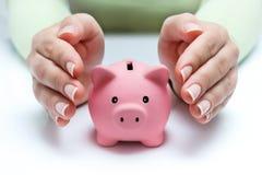 Protégez votre épargne - avec les mains et la tirelire Image stock
