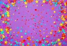 Protagoniza confeti en un fondo púrpura Fotografía de archivo libre de regalías