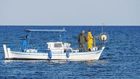 Protaras, Chipre - 3 de febrero de 2016: El pescador nada en su barco de pesca en el mar metrajes