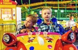Night view to kids riding amusement cars on carousel. PROTARAS, CYPRUS - SEPTEMBER 23, 2017: Night view to kids looking towards camera and riding amusement cars Royalty Free Stock Photos