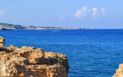 Protaras, the island of Cyprus. Mediterranean coastline. Beautiful day, blue sky, foamy waves of the azure sea roll to the rocky