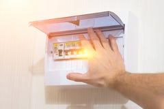 Proteção da instalação elétrica que ajusta o painel de comando, interruptor sobre por choque elétrico da mão fotografia de stock royalty free