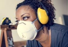 Proteção de orelha vestindo do contramestre da mulher negra fotografia de stock royalty free