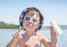 A proteção solar está na cara do menino do moderno antes de bronzear-se durante férias de verão na praia Fotos de Stock
