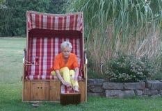 A proteção solar não foi esquecida pela mulher atrativa na cadeira de praia de vime telhada foto de stock royalty free