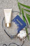 Proteção solar, vidros, escudo, passaporte, tampões de ouvido na areia fotografia de stock