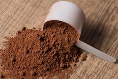 Proteína do soro Colher branca no fundo de madeira com chocolate po foto de stock