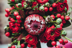 Protea and ranunculuses Bouquet on a blured gray background.  Royalty Free Stock Images
