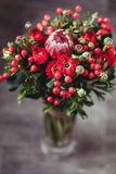 Protea and ranunculuses Bouquet on a blured gray background.  Stock Images