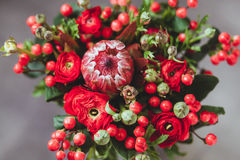 Protea and ranunculuses Bouquet on a blured gray background.  Royalty Free Stock Photos