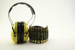 Protección auditiva amarilla y correa de la munición del camuflaje Imagenes de archivo