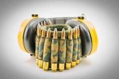 Protección auditiva amarilla y correa de la munición del camuflaje Fotografía de archivo libre de regalías