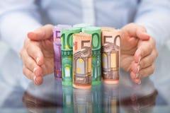 Protección de la mano rodada encima de billete de banco euro Imagen de archivo libre de regalías