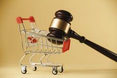 protección de las derechas de consumidor Martillo del juez con una carretilla en un fondo blanco Primer foto de archivo libre de regalías