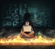 Protección del cortafuego Hombre que trabaja en el ordenador portátil delante de un cortafuego foto de archivo libre de regalías