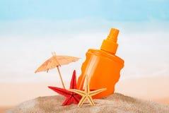 Protección solar, paraguas y estrellas de mar en la arena contra el mar Imagen de archivo libre de regalías