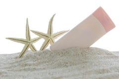 Protección solar y estrellas de mar en la arena imagenes de archivo