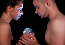 Protect the earth. Couple holding and protecting an illuminated earth royalty free stock photos