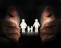 Protect family. Paper cut of family icon cover by hands Stock Photos
