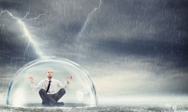 Protect the financial and economic serenity. Businessman safely inside a sphere during a storm . Protect the financial and economic serenity stock photos