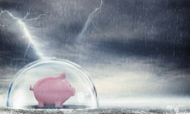 Protect gains from the crisis. Piggybank safely inside a sphere during a storm . Protect gains from the crisis stock images