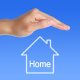 Protect Home. A hand protecting the home royalty free stock image