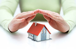 Protect and insurance real estate concept. House covered of hands Royalty Free Stock Image
