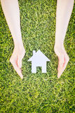 Protect or Insure a Home. House insurance or safety concept - two hands of a young woman protect a white cutout paper house over grass Stock Photography