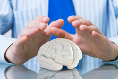 Protect mental health. Hands of man holding with care human brain Stock Images