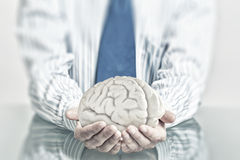 Protect mental health. Hands of man holding with care human brain Royalty Free Stock Image