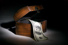 Protect money. Hundred dollars and wooden chest. A black background. Beautiful illumination stock photos