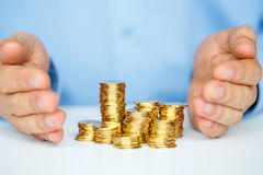 Protect new business start-up  - with hands and coin Stock Photo