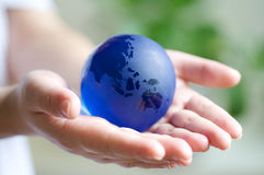 Protect our planet. Women hand holding a sapphire quartz planet earth royalty free stock photos