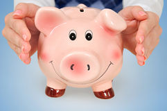 Protect piggy bank. On blue table royalty free stock photography